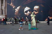 A young boy reaches up to touch a Yoda busker and other passers-by in front the faces from The Taking of Christ c1602 the painting of the arrest of Jesus, by Italian Baroque master Caravaggio and exhibited, on 30th September 2016, at the National Gallery, London, England.
