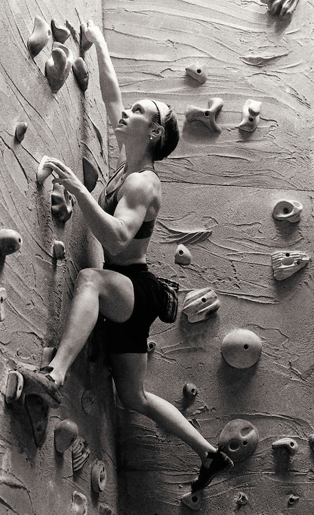 Young woman practicing rock climbing indoors, low angle view (B&W)