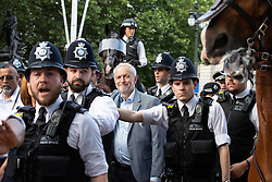 © Licensed to London News Pictures . 13/07/2018. London, UK. JEREMY CORBYN is lead from Trafalgar Square along The Mall , Horse Guards Parade and across Whitehall by dozens of police after speaking to thousands of demonstrators in Trafalgar Square at a rally in protest against US President Donald Trump's UK visit . Photo credit: Joel Goodman/LNP