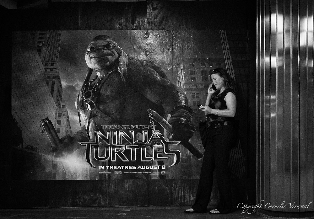 Lady talking on one cell phone while texting on another as the Ninja Turtles are about to take Manhattan.<br /> Seen at Grand Central Terminal