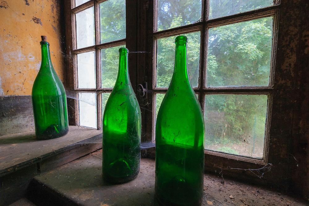 Old calvados bottles at Château du Breuil in Normandy, France.