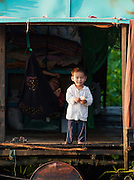 A young boy stands on the doorstep of his floating house in one of the floating village communities on the great Tonlé Sap lake, Cambodia
