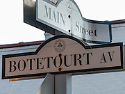 """Signs mark the corner of Main Street and Botetourt Avenue in Gloucester Court House, Virginia, USA. Known and remembered in Virginia as """"Lord Botetourt,"""" Norborne Berkeley, 4th Baron Botetourt (1718-1770) was governor of the Colony of Virginia from 1768 to 1770 and a member of Board of Visitors of the College of William & Mary at the capital of the Colony in Williamsburg, Virginia. Gloucester County Court House Square Historic Historic District is a state Historic Landmark. Keeping its rural character, Gloucester County is part of the Hampton Roads metropolitan area in the Commonwealth of Virginia, USA. Formed in 1651 in the Virginia Colony, the county was named for Henry Stuart, Duke of Gloucester, third son of King Charles I of Great Britain. Located in the Middle Peninsula region, the county borders the York River and the lower Chesapeake Bay, about 75 miles east of Virginia's capital, Richmond. Gloucester County was the site of Werowocomoco, a capital of the large and powerful Native American Powhatan Confederacy, which affiliated 30 tribes under a paramount chief. It was home to members of early colonial First Families of Virginia and important leaders in the period up to the American Revolutionary War."""