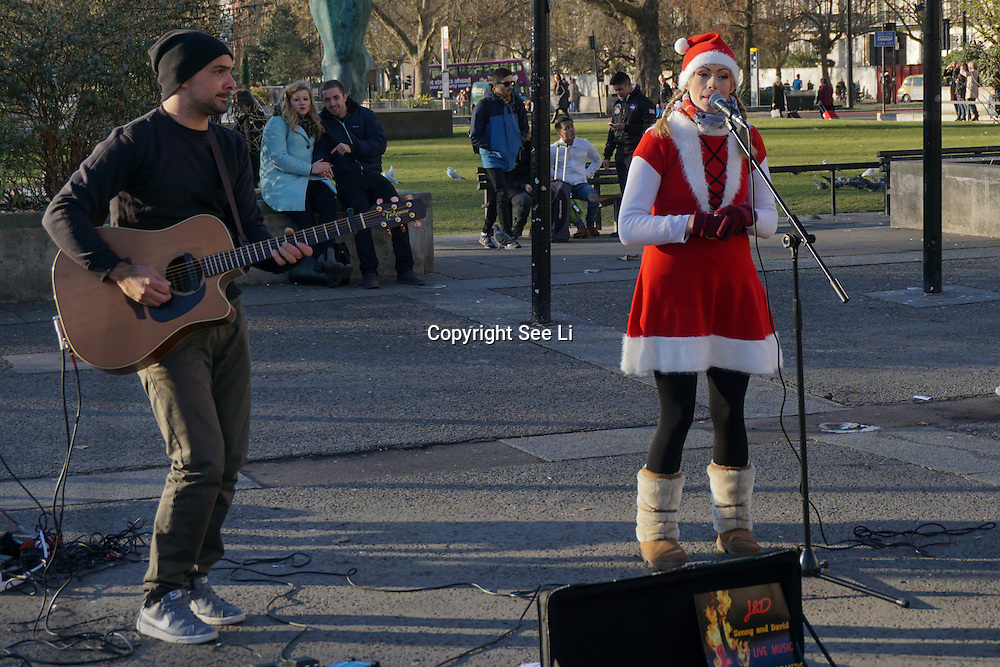 Sun and cold winter tourist's watching people buskers Busking in Marble Arch on 4th December 2016,London,UK. Photo by See Li