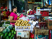07 AUGUST 2017 - BEBANDEM, BALI, INDONESIA: A woman sells fruit in the market in Bebandem, in far eastern Bali. The market is known for baskets, which are woven in the area. Bali's local markets are open on an every three day rotating schedule because venders travel from town to town. Before modern refrigeration and convenience stores became common place on Bali, markets were thriving community gatherings. Fewer people shop at markets now as more and more consumers go to convenience stores and more families have refrigerators.     PHOTO BY JACK KURTZ