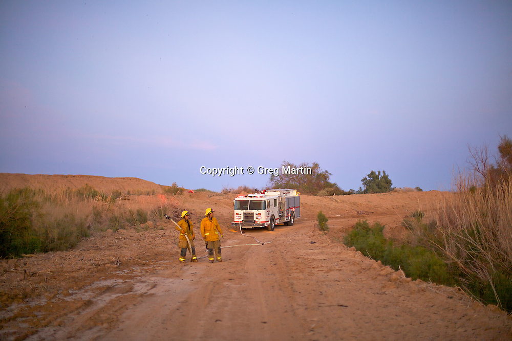 Firemen in position to stop a wildfire from crossing the road.
