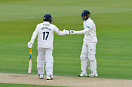 Sam Northeast of Hampshire touches gloves with Aiden Markram of Hampshire after a boundary during the first day of the Specsavers County Champ Div 1 match between Hampshire County Cricket Club and Essex County Cricket Club at the Ageas Bowl, Southampton, United Kingdom on 5 April 2019.