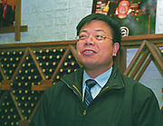 Liang Xeujun, Chief Engineer / Oenologist at the Beijing Dragon Seal Wines Cp Ltd winery in front of a wine rack Beijing, China, Asia