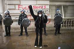 © Licensed to London News Pictures. 06/06/2020. London, UK. A protester raises a fist in front of Police officers while gathering in Westminster, central London to take part in a Black Lives Matter demonstration over the killing of African American George Floyd. The death of George Floyd, who died after being restrained by a police officer In Minneapolis, Minnesota, caused widespread rioting and looting across the USA. Photo credit: Ben Cawthra/LNP