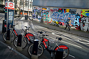 Santander rental bikes await their next riders, in front of a pedestrian in Shoreditch where graffiti covers the exterior of a former office property, on 26th February 2021, in London, England.