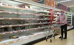 © Licensed to London News Pictures. 07/10/2021. London, UK. A shopper wearing a face covering looks at nearly empty shelves of pre-cooked meat products in Sainsbury's, north London just after 9am. The Government and retailers warn that food and fuel shortages could continue until Christmas due to labour shortages following Brexit. Photo credit: Dinendra Haria/LNP