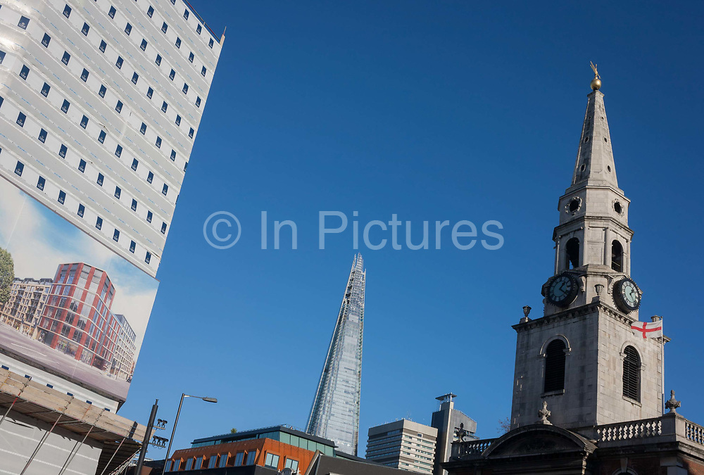The new Shard tower rises high above London next to new housing and the spire of St George the Martyr church at Marshalsea, on 28th November 2016, in Borough, Southwark, England. The church is a Grade II* listed building whose earliest reference is in 1122 though its strong associations are with Charles Dickens, whose father was imprisoned for debt in the Marshalsea prison. The Shard 2012 is at 310 m 1,017 ft tall, the tallest building in the European Union.