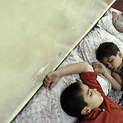 Brothers (left to right) Waheed Dost age 12, Nazir age 13 and Javid age 16 sleep on the floor of their apartment.  This family of eleven has no beds and so the parents and nine children sleep on blankets and pillows laid out on the floor of their apartment.  Photo by Louie Palu/The Globe and Mail ©
