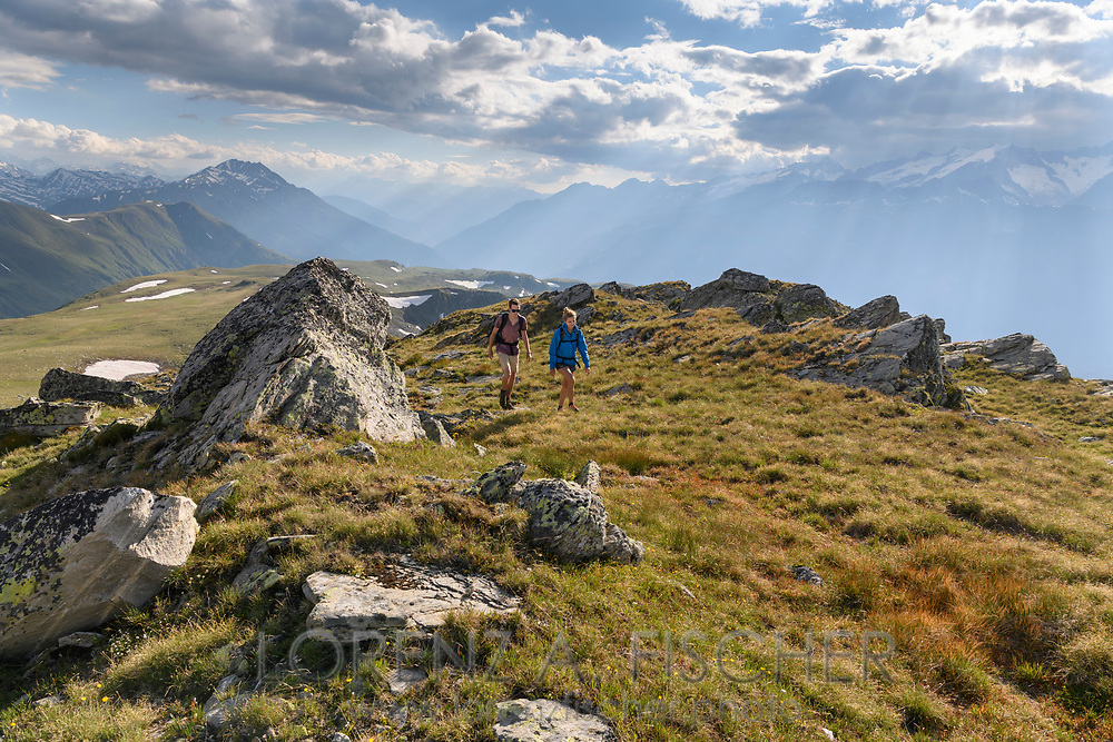 A hiker couple on the Ärnergalen looking down the main valley with peaks of the Bernese Alps, Landschaftspark Binntal, Valais, Switzerland