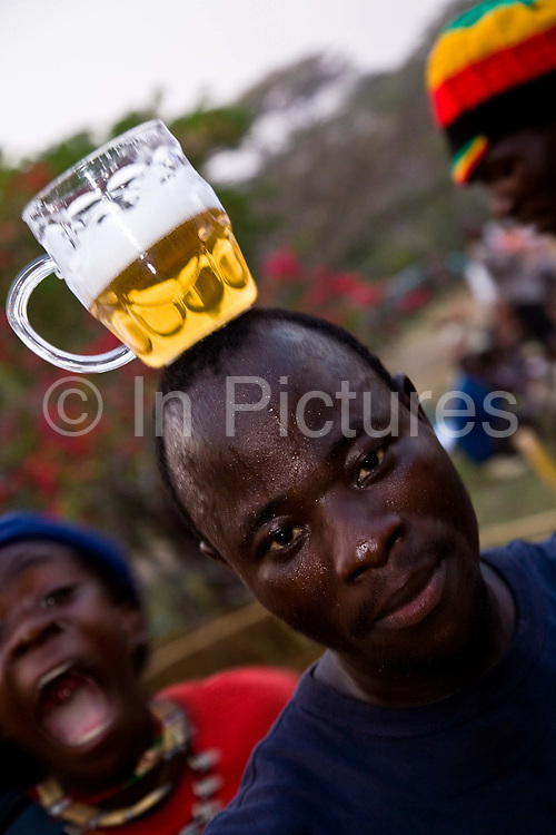 Malawian men drink and dance dancing to the sounds of African bands and UK based Dj's  during the Lake of Stars music festival, Chinteche, Malawi.