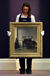 © Licensed to London News Pictures. 17/05/2013. London, UK An assistant holds VILHELM HAMMERSHØI. DANISH.1864 - 1916. IDA IN AN INTERIOR WITH PIANO.Estimate: 1,000,000 - 1,500,000 GBP .A photo call for a preview of 19th Century European Paintings held at Sotheby's London today 17th May 2013. The paintings will be offered to auction on 23 May 2013. Photo credit : Stephen Simpson/LNP