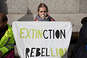 Despite a directive from the police not to gather, Extinction Rebellion take over Trafalgar Square in protest where they gathered for speeches some taping up their mouths as if silenced on 16th October 2019 in London, England, United Kingdom. Extinction Rebellion is a climate change group started in 2018 and has gained a huge following of people committed to peaceful protests. These protests are highlighting that the government is not doing enough to avoid catastrophic climate change and to demand the government take radical action to save the planet.
