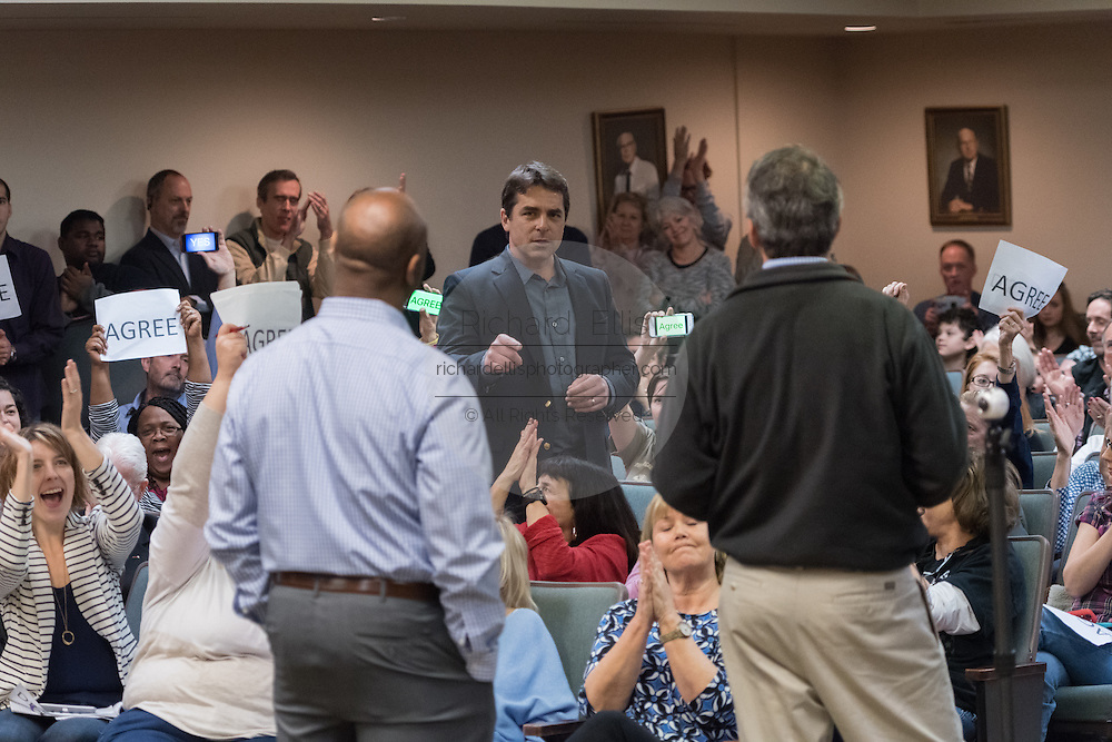 A man expresses his concerns about President Donald Trump to U.S. Sen. Tim Scott, left, and U.S. Rep. Mark Sanford as members of the audience voice their support during a town hall meeting February 18, 2017 in Mount Pleasant, South Carolina. Hundreds of concerned residents turned up for the meeting to address their opposition to President Donald Trump during a vocal meeting held by U.S. Rep. Mark Sanford and Senator Tim Scott.