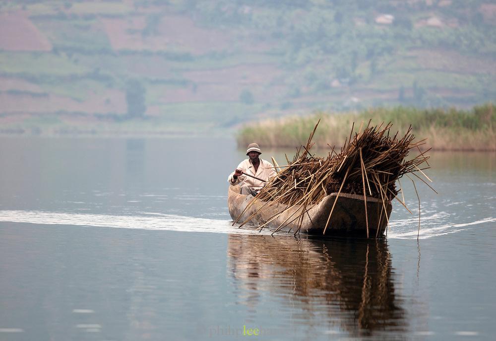 Man transporting reeds in Lake Bunyonyi, South West Uganda