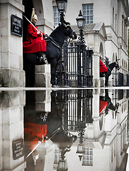 © Licensed to London News Pictures. 03/10/2020. London, UK. Mounted troopers of the Household Cavalry on duty at Horse Guards are reflected in rainwater after heavy overnight rain as Storm Alex affects parts of the south. Photo credit: Peter Macdiarmid/LNP