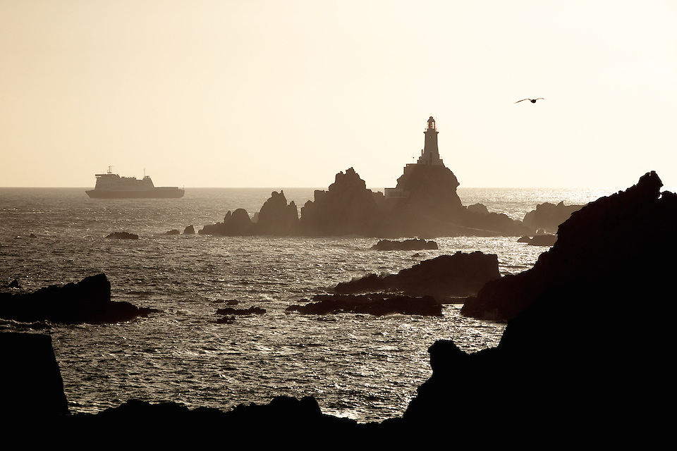 Condor Ferries ship sailing behind the tourist attraction Corbiere Lighthouse in Jersey, Channel Islands