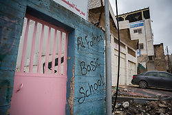 2 March 2020, Hebron: The Al Faihaa Basic School in the H2 area of Hebron, an area of the city which is under Israeli military control. Palestinians cannot enter into the area unless they have residence there, and even then, cannot drive a Palestinian car inside the area. Just next to the school is a home of a Palestinian family (right) who have seen two of their floors confiscated by Israeli settlers, who now live on top of them.