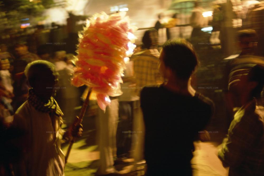 A hawker sellign cotton sugar during Dussera festival in New Delhi, October 2004