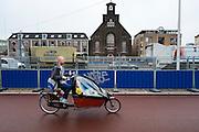 Een man fietst met twee kinderen in de bakfiets langs de bouwplaats voor de aanleg van de Catherijnesingel in Utrecht.<br /> <br /> A man is cycling with two children in a cargo bike near the construction area in Utrecht.