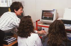 Teacher and secondary school pupils using computer,