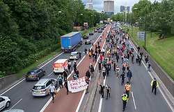 """© Licensed to London News Pictures; 03/07/2021; Bristol, UK. Kill the Bill protesters carry a banner saying """"Priti Shit New Law"""" in reference to the Home Secretary Priti Patel and the Police, Crime, Sentencing and Courts Bill up the M32 motorway during a fourteenth """"Kill the Bill"""" protest in Bristol against the Police, Crime, Sentencing and Courts Bill during the Covid-19 coronavirus pandemic in England. Protesters marched up the M32 and blocked traffic for a time. The Police, Crime, Sentencing and Courts Bill proposes new restrictions on protests and is due to return to the House of Commons for debate on Monday 05 July. Some previous Kill the Bill protests in Bristol had violence. Photo credit: Simon Chapman/LNP."""