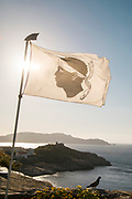 Close up of flag on wind, sea in background, Calvi, Corsica, France