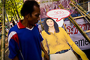 "11 MAY 2013 - BANGKOK, THAILAND:  A protesting farmer walks past a cardboard cutout of Thai Prime Minister Yingluck Shinawatra. Several hundred small scale family farmers camped out ""Government House"" (the office of the Prime Minister) in Bangkok to Thai Prime Minister Yingluck Shinawatra to deliver on her promises to improve the situation of family farmers. The People's Movement for a Just Society (P-move) is a network organization which aims strengthen the voices of different, but related causes working to bring justice for marginalized groups in Thailand, including land rights for small-scale farmers, citizenship for stateless persons, fair compensation for communities forced to relocate to accommodate large scale state projects, and housing solutions for urban slum dwellers, among others.   PHOTO BY JACK KURTZ"