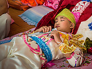 "04 APRIL 2015 - CHIANG MAI, CHIANG MAI, THAILAND: A boy sleeps in his family's quarters at Wat Pa Pao during the Poi Sang Long Festival. The Poi Sang Long Festival (also called Poy Sang Long) is an ordination ceremony for Tai (also and commonly called Shan, though they prefer Tai) boys in the Shan State of Myanmar (Burma) and in Shan communities in western Thailand. Most Tai boys go into the monastery as novice monks at some point between the ages of seven and fourteen. This year seven boys were ordained at the Poi Sang Long ceremony at Wat Pa Pao in Chiang Mai. Poy Song Long is Tai (Shan) for ""Festival of the Jewel (or Crystal) Sons.      PHOTO BY JACK KURTZ"