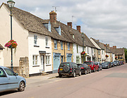 Cars parked on street frontage outside historic building in Saxon town of Cricklade, Wiltshire, England, Uk