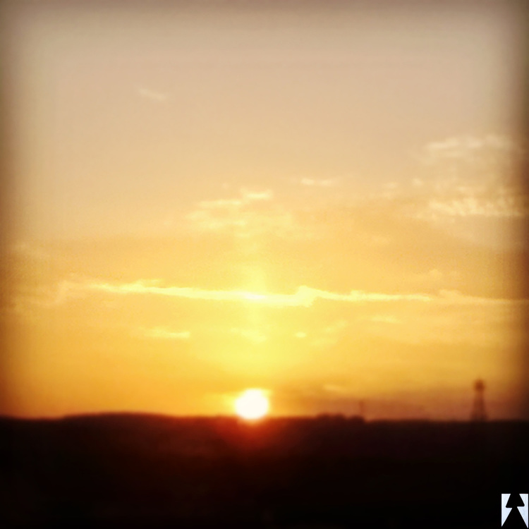 Texas sunrise bright deep yellow full sun shimmering clouds violet sky old-time oil well.