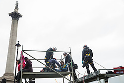 London, UK. 7 October, 2019.  A climate activist from Extinction Rebellion is removed by a specialist team of Metropolitan Police officers from a scaffold tower used to block Trafalgar Square on the first day of International Rebellion protests to demand a government declaration of a climate and ecological emergency, a commitment to halting biodiversity loss and net zero carbon emissions by 2025 and for the government to create and be led by the decisions of a Citizens' Assembly on climate and ecological justice.