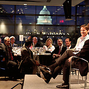 Tucker Carlson interviews author Michael Lewis at corporate dinner meeting with US Capitol dome in background