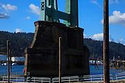 USA, Oregon, Portland, Cathedral Park, man taking close-up look at St. John's Bridge. MR