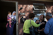 Kawthar Alsaloum, 23, holds daughter Jamila, 2, in the doorway of their temporary apartment on the day they moved in, in Tampa, Florida, U.S. The family's resettlement case manager, Rana Al Sarraf (second from R) discusses the apartment's condition and temporary nature with Coptic Orthodox Charities executive director Amira Salama (in green) and Zeyad Abduljaber of sister organization Radiant Hands.