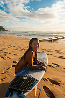 A female surfer takes a break on the beach, Manly Beach, Sydney, New South Wales, Australia