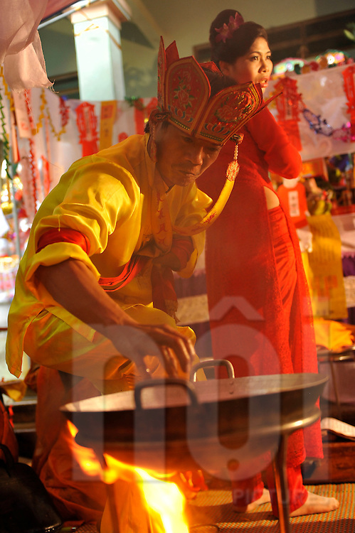 Medium extracts boiling oil during Pha do gia Tien festival, Ta Tien Village, Hung Yen Province, Vietnam, Southeast Asia