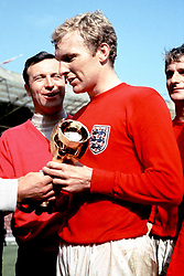 England captain Bobby Moore (c) is congratulated by squad member Jimmy Armfield (l) as he clings onto the Jules Rimet trophy following England's 4-2 win