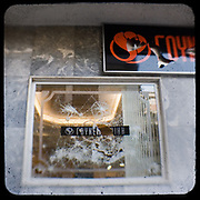 A smashed window of a fur shop on Sina Street. <br /> <br /> Following the murder of a 15 year old boy, Alexandros Grigoropoulos, by a policeman on 6 December 2008 widespread riots, protests and unrest followed lasting for several weeks and spreading beyond the capital and even overseas<br /> <br /> When I walked in the streets of my town the day after the riots I instantly forgot the image I had about Athens, that of a bustling, peaceful, energetic metropolis and in my mind came the old photographs from WWII, the civil war and the students uprising against the dictatorship. <br /> <br /> Thus I decided not to turn my digital camera straight to the destroyed buildings but to photograph through an old camera that worked as a filter, a barrier between me and the city.