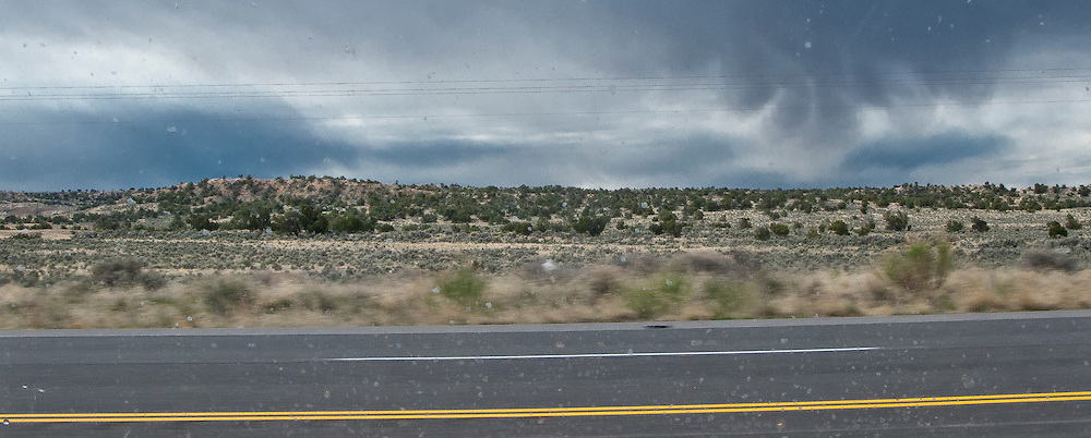 strange cloud and arid landscape through a water spotted auto window and parallel power lines across the panorama image along US 550 in NW New Mexico, USA