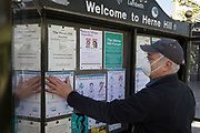 As the UK government considers further restrictions of movement in public places during the Coronavirus pandemic, a member of local community group, the Herne Hill Forum, attaches health guidelines printed off from the BBC, to help south Londoners understand all precautions necessary to keep them safe virus-free, on 23rd March 2020, in London, England.