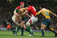 Matt Giteau of Australia is tackled by Alun-Wyn Jones and Jonathan Thomas of Wales .Invesco Perpetual series, Wales v Australia at the Millennium Stadium on Saturday 28th Nov 2009.  pic by Andrew Orchard, Andrew Orchard sports photography, .EDITORIAL USE ONLY