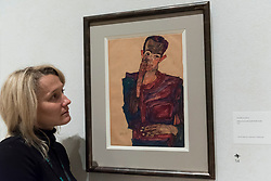"""© Licensed to London News Pictures. 31/10/2018. LONDON, UK. A staff member views """"Self-portrait with Eyelid Pulled Down"""", 1910, by Egon Schiele. Preview of """"Klimt / Schiele:  Drawings from the Albertina Museum,Vienna"""" exhibition at the Royal Academy.  Over 100 works on paper are on display in an exhibition which marks the centenary of the deaths of the two most celebrated and pioneering figures of early twentieth-century art.  The show runs 4 November to 3 February 2019.  Photo credit: Stephen Chung/LNP"""