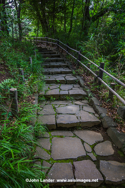 """At first, the Philosophy Park just appears to be a rather large and pleasant expanse of greenery and hills north of Nakano.  Local inhabitants use it to job, walk the dog, and have a picnic.  Look a little closer, however, and the place is quite unusual for any city park, anywhere on Earth.  The guy who developed the park thought he could bring concepts to life or at least show them through physical objects or statues.  Pass through the Tetsurimon, or the Gate of Philosophical Reason, and voila - you just might become enlightened in here!  Statues of Gandhi and others will remind you of a higher calling.  In fact, there are  77 spots that symbolize different philosophical doctrines. Notable features of the park are the Rokkendai or Pagoda of the Six Wise Ones which serves as the icon for the park.  Two trails that cross, The Junction of Doubt, which is a kind of """"road not taken"""" syndrome.  And of course Rito the tanuki lamp.  Tanuki of course assume the form of humans to trick us, but they also have a divine nature.  Tetsugakudo Philosophy Park was founded by philosopher Enryo Inoue, who wanted to enshrine philosophical theory into physical form. Inoue founded the Tetsugakukan, or Philosophy Academy which is now Toyo University.  For him, philosophy was an essential discipline for the sake of spiritual aspects and scholarship so as to improve life.  Otherwise, the place is very pleasant with floral plantings, mossy trails, plenty of benches and hidden gazebos and huts that are perfect for a picnic lunch."""