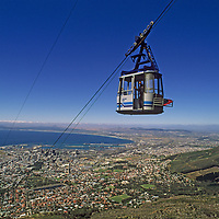 A cable car climbs above Cape Town, South Africa, en route to the summit of Table Mountain. In the background False Bay stretches towards the Cape of Good Hope (not visible), where the Atlantic and Indian Oceans meet.