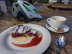 Outdoor restaurant table with coffee cup and pastry, Ferme Auberge Seestadle, France